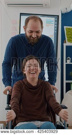 Cheerful Young Man Pushing Wheelchair With His Disabled Paralysed Invalid Coworker While Smiling In