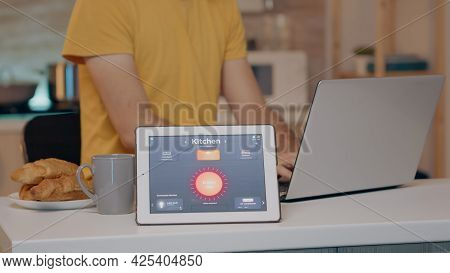 Male Typing On Laptop Working From Home With Automation Lighting System Using Voice Controlled App O