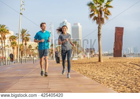 Running interracial couple friends talking while training together on morning beach run exercise. Fitness people runners, Barcelona Beach. Multiracial athletes jogging. Sport summer active lifestyle.