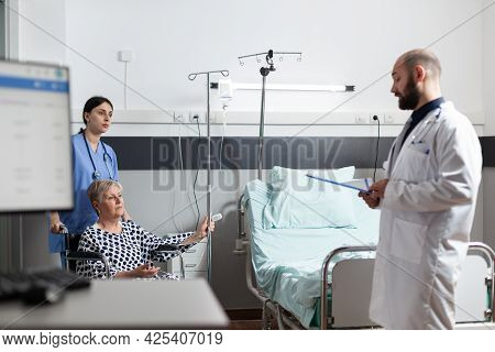 Senior Woman Getting Medicine Through Intravenous Line Bag Sitting On Wheechair Pushed By Nurse In H
