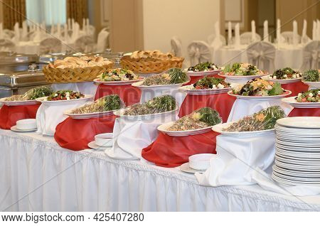 Catering A Lot Of Salads From Vegetables And Meat On A White And Red Tablecloth In A Large Banquet H
