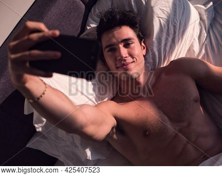 Attractive Young Man Using Cell Phone To Take Selfie Photo