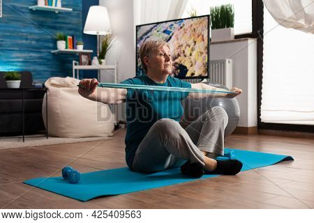 Retired Senior Woman Sitting On Yoga Mat In Lotus Position Stretching Arms Muscles Using Stretch Ela