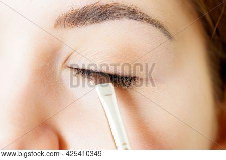 Face Painting, Closeup. Makeup Artist Applying Black Eyeliner To Model Eye, Using Flat Liner Brush.