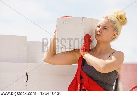 Strong Pretty Woman Working On Construction Site, Building House, Installing Gray Airbricks. Industr