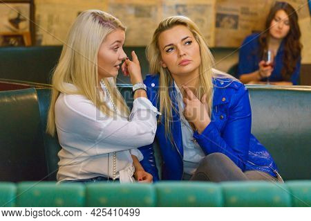 Women Two Girlfriends Gossiping About Third, Sad Girl With Alcohol Glass In The Background. Friendsh
