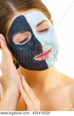 Woman With Clay Carbo Black Mask On Half Face And White Mud On Second Half. Girl Taking Care Of Oily