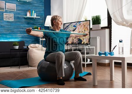 Cheerful Retired Pensioner Working Arm Muscles Using Elastic Band Practicing Aerobic Exercise. Pensi
