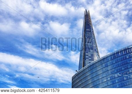 London, UK - 29 September 2016: The News building and The Shard, with small plane and summer blue sky background.. Designed by Renzo Piano, The News Building is home News UK London operations.