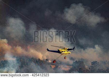 Two Helicopters With Bambi Bucket Team Working On Fire Extinction