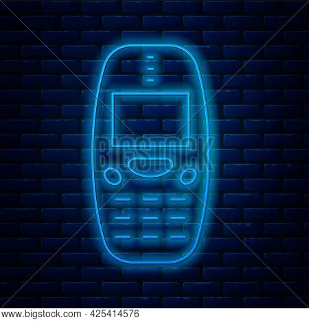 Glowing Neon Line Old Vintage Keypad Mobile Phone Icon Isolated On Brick Wall Background. Retro Cell