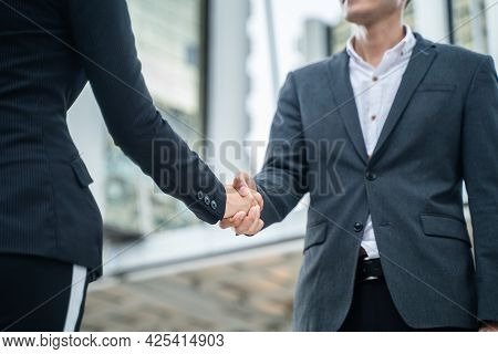 Close Up Of Asian Young Business Man Greeting And Making Handshake In The City. Partnership Worker A