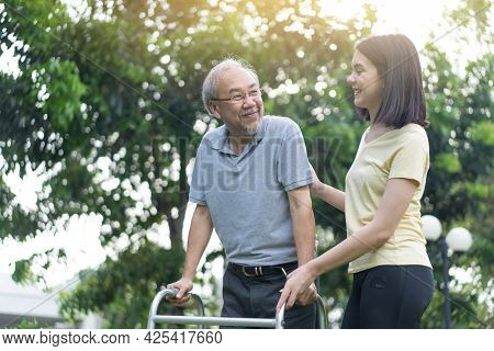 Asian Young Beautiful Girl Daughter Take Care Of Disabled Senior Elderly Grandfather In Garden. Attr