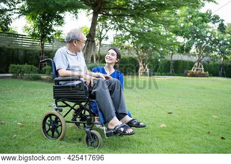 Asian Young Woman Nurse At Nursing Home Take Care And Support Disabled Senior Elderly Man On Wheelch