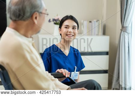 Asian Attractive Nurse Taking Care Of Mature Senior Elderly Male Patient Sitting On Wheelchair At Ho