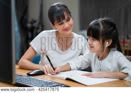 Homeschool Asian Little Young Girl Learning Online Class From School Teacher By Digital Remote Inter