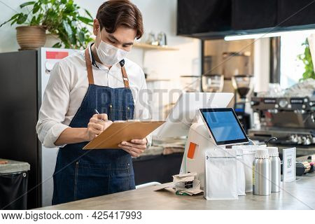 Asian Cafe Business Male Owner Checking Takeaway Order From Clipboard. Restaurant Barista Worker Pre