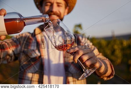 Positive Male Winemaker Pouring Fine Rose Wine From Bottle Into Glass While Standing Against Blurred