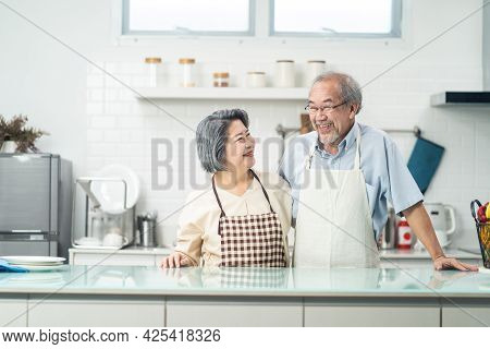 Portrait Of Asian Senior Elderly Couple Wear Apron In Kitchen At Home. Happy Loving Older Grandfathe