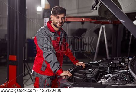 Side View Of Professional Repairman In Workwear Looking At Camera And Smiling Friendly While Standin