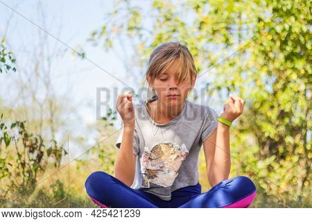 Defocus Caucasian Preteen Girl Practicing Yoga In Park, Forest, Outdoor, Outside. Meditation And Con