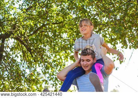 Defocused Brother Riding Sister On Back. Portrait Of Happy Girl On Man Shoulders, Piggyback. Girl Fl