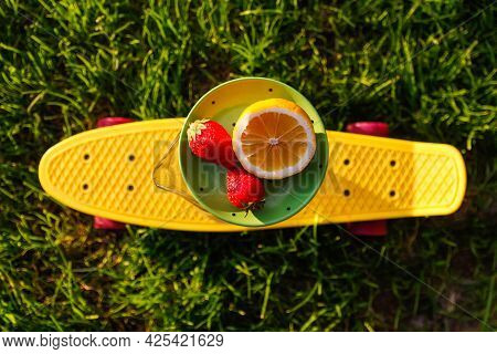 Defocus Close-up Saucer With Lemon And Two Strawberry Standing On Glass Jug Of Lemonade On Yellow Pe