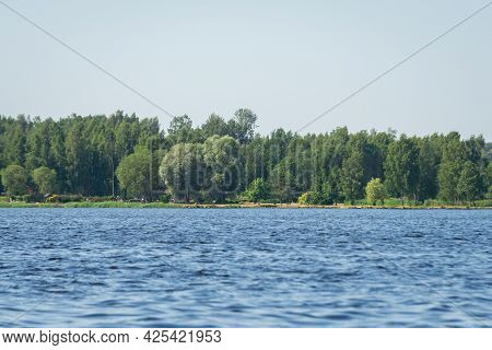 Summer Landscape With Blue Skies And Blue Wavy Water Of A Forest Lake. In The Middle Of A Warm, Sunn