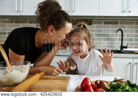 Cute Mom Leaning Against Her Little Daughter While Making Dough. Mother And Daughter Prepare Dough T