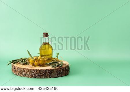 Virgin Olive Oil Bottle And Green Olives On Green Background. Copy Space
