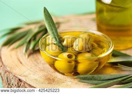 Virgin Olive Oil Bottle And Green Olives On Green Background