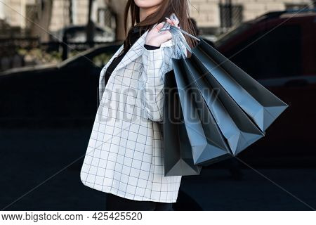 Girl In Jacket Holds Several Shopping Bags On Black Background. Black Friday, Sale, Discount.