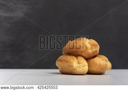 Profiteroles Or Popovers, Eclairs Side View. Three Appetizing Profiteroles. Gray Background