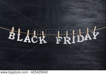 Words Black Friday With Clothespins On Black Background. Discounts. Sale.