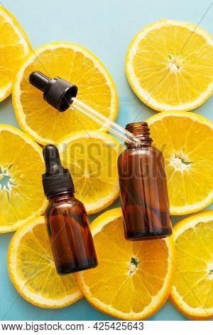 Brown Glass Bottle With A Pipette Serum With Vitamin C. Essential Oil And Orange Slices. Health And