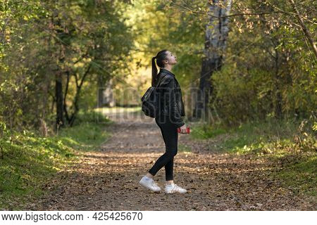 Girl Student Walks In The Autumn Park. Stylish Young Woman Walks In The Forest. Alley With Yellow Fa