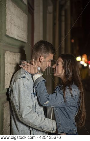 Smiling Young People Hug In The Street. Evening Date, Young Couple In Love. Beautiful Girl Hugs A Gu