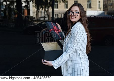 Brunette Woman Opened Gift Box Looking At Camera And Smiling. Happy Girl With Gift On The Street.