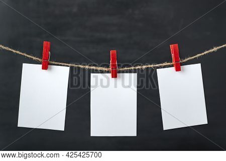 White Blank Paper Cards Hang With Clothespins On Rope. Black Background. Copy Space, Mockup.
