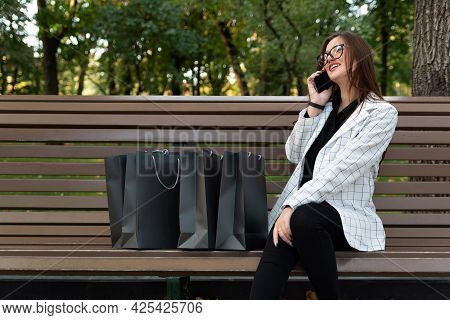 Young Woman Sits In The Park On Bench Next To Shopping Bags And Talks On Phone.