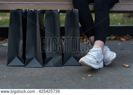Womens Feet In Sneakers And Paper Shopping Bags. Black Friday Discounts.