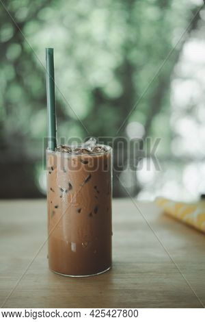 Iced Mocha Coffee In Glass With Green Straw On Wood Table