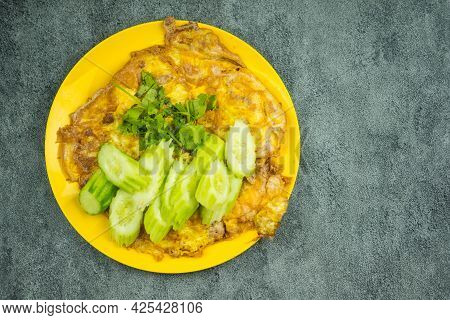 Above View Of Omelet Served With Cucumber And Cilantro In Yellow Plate. Omelet Egg Fry Popular Tradi