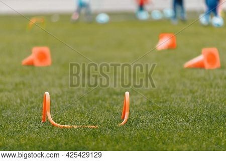 Football Training Equipment On Grass Pitch. Orange Practice Hurdle And Training Cones. Players Runni