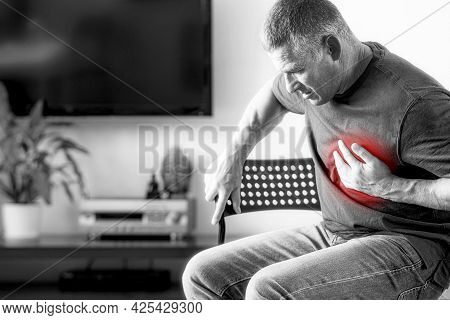 Man Experiences Chest Pain Caused By A Heart Attack. Heart Disease In An Elderly Man With A Black-an