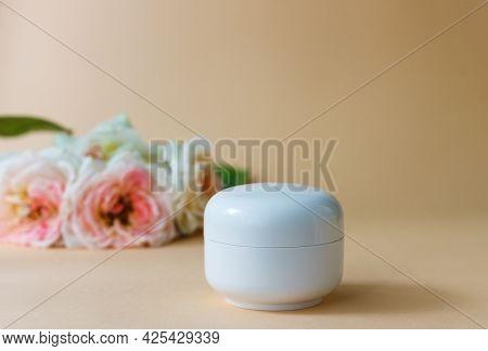 Jar Of Moisturizer Cream On A Background Of Beige Roses. Plastic White Jar Of Sensitive Skin Cream O