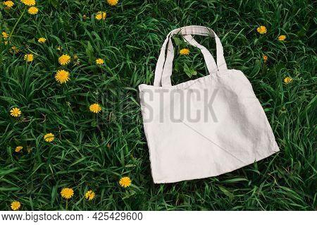 White Cotton Or Mesh Bag On Dandelion Grass Background. Zero Waste, No Plastic, Eco Friendly Shoppin