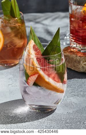 Strawberry Gin Tonic cocktail for lifestyle design. Summer cocktail concept background. Gin and Tonic drink with grapefruit slice, strawberry and banana leaf. Cocktail glass on vintage table