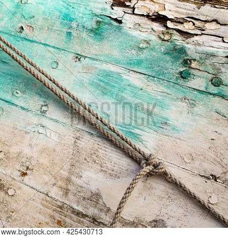 Old and colored boat wooden hull, old painting with green and white cracks and wood texture