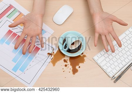 Closeup Of Woman Spilled Coffee On Wooden Office Desk, Top View